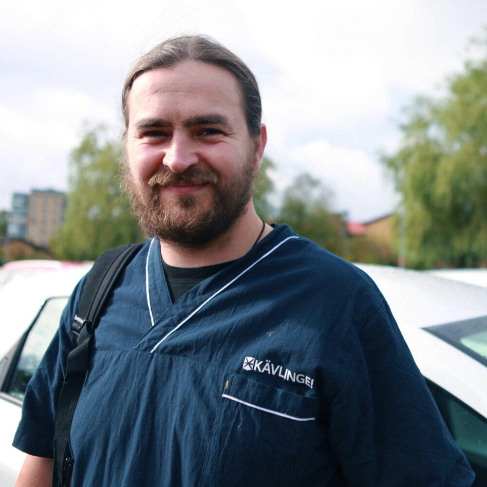 Glad man i medelåldern med skägg poserar i mörkblå vårdkläder på parkeringsplats.