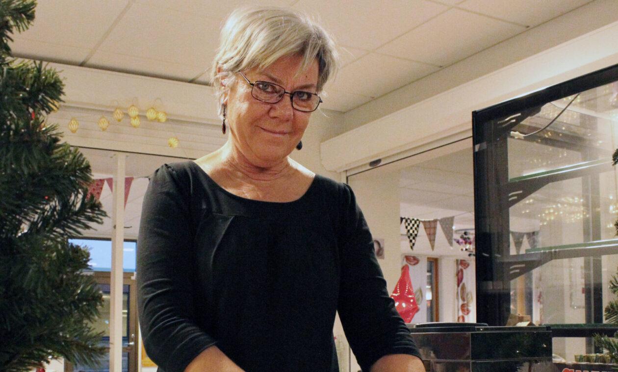 Carina Nilsson tittar upp och möter kameran då hon brer smör på en delad fralla.