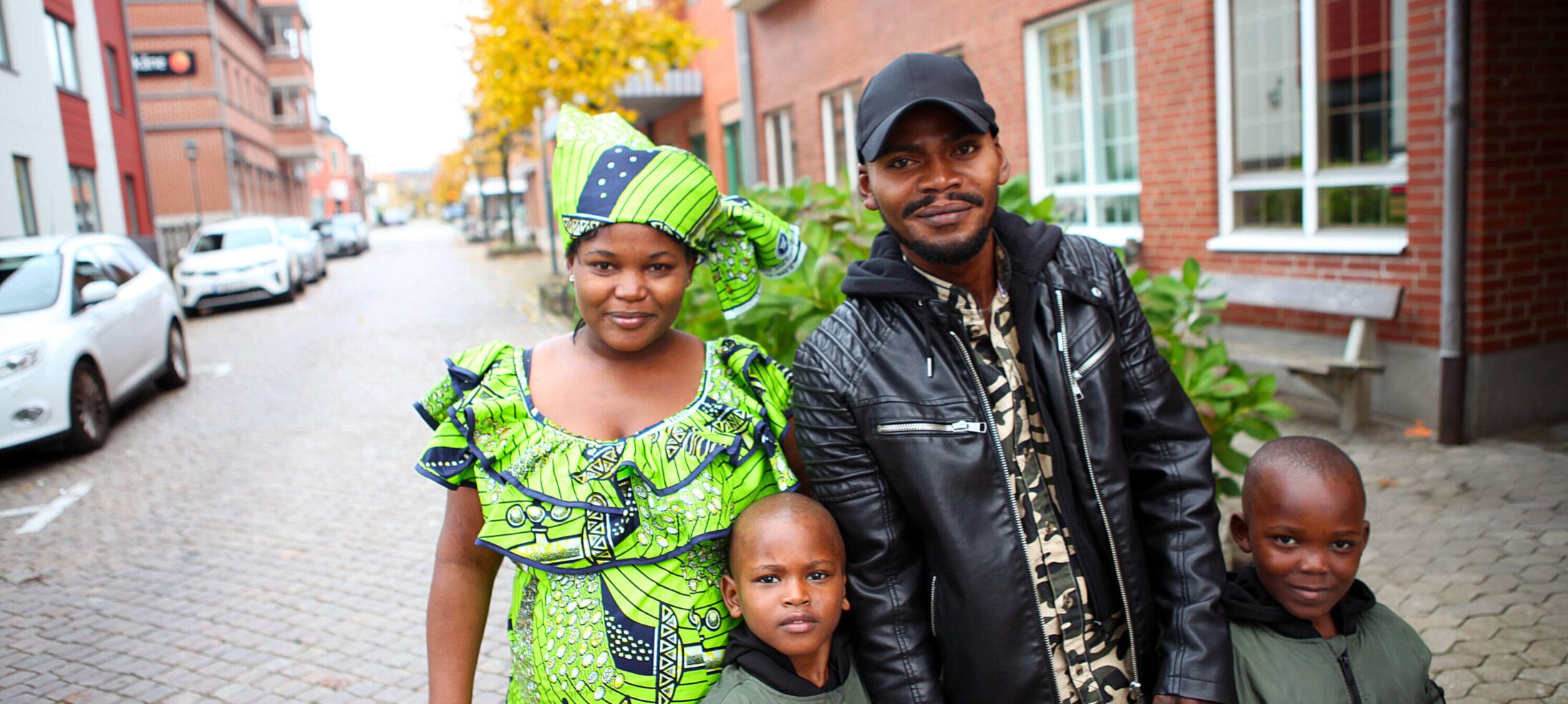 Mamma, pappa och två barn poserar utomhus för kameran. Mamman har färgglada kläder från sitt hemland i Afrika.