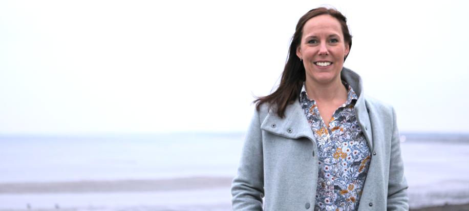 Katarina Hillertz poserar i grå kappa och mönstrad blus på stranden i Barsebäck en gråmulen dag.