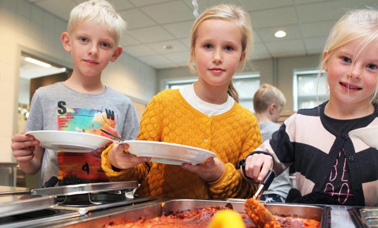 Tre barn, en pojke och två flickor, tar mat i skolmatsalen och tittar in i kameran.