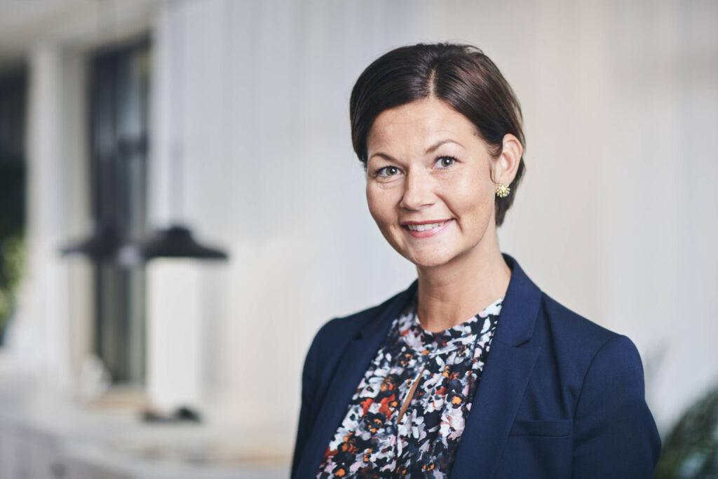 Bild på Lina Rosenstråle i blå kavaj med mönstrad blus inifrån Kommunhuset.