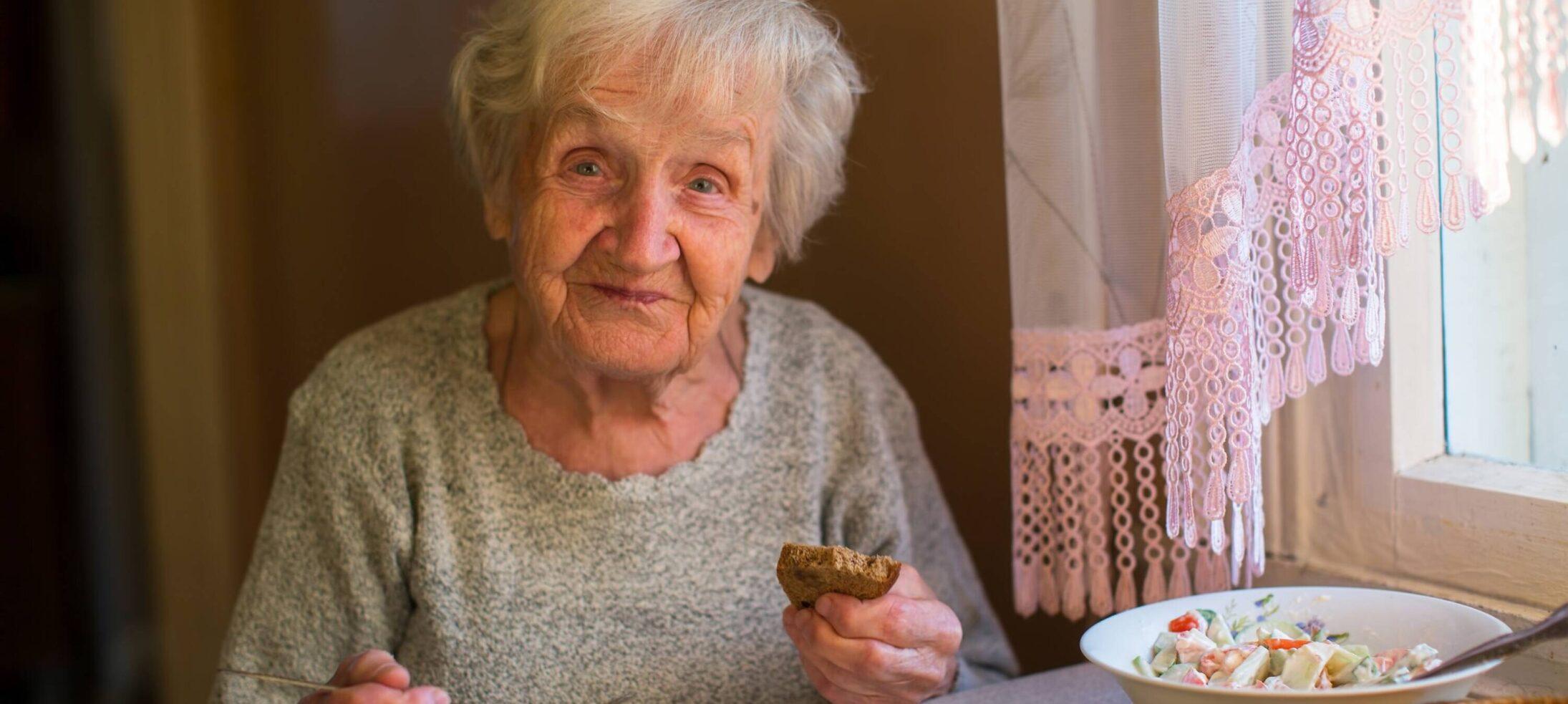 Äldre dam med vitt hår sitter och äter vid sitt köksbord.