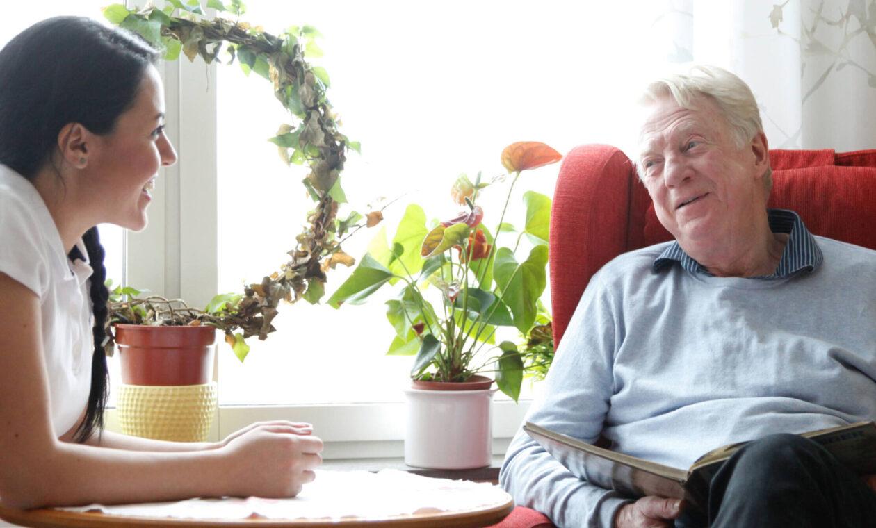 Äldre man med vitt hår i röd öronlappsfåtölj samtalar med ung flicka i tjugoårsåldern som vilar armbågarna på bordet dem emellan.