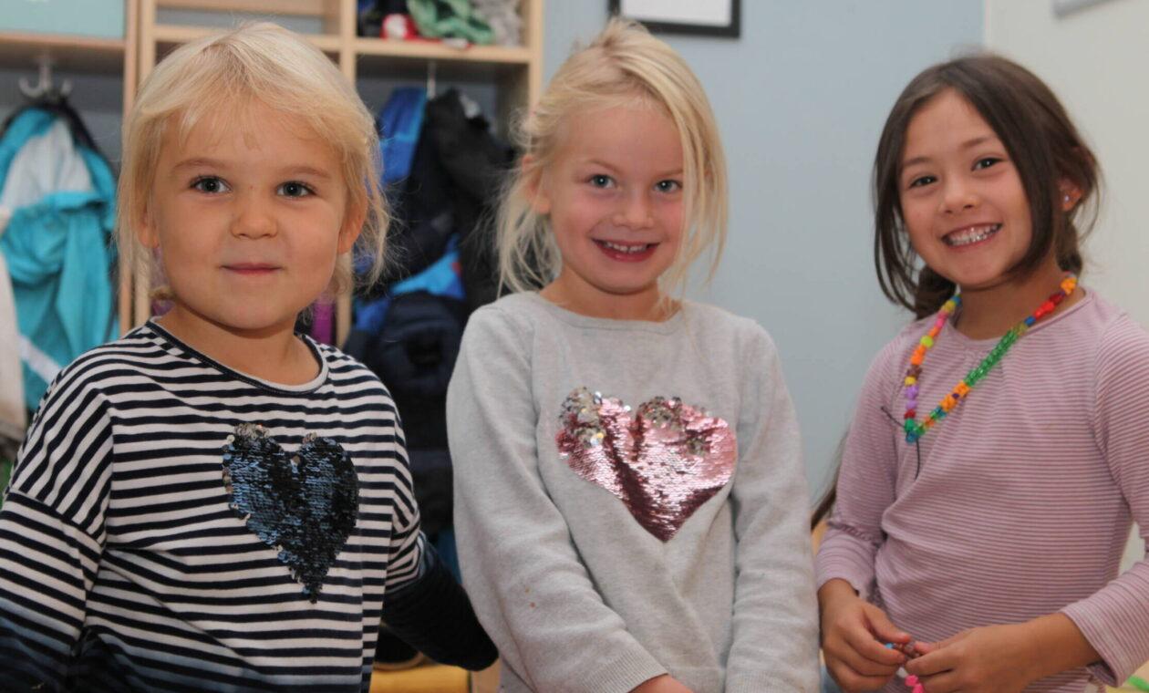 Tre små flickor poserar i kapprummet på förskolan.