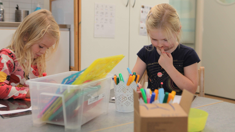 Två små flickor pysslar koncentrerat vid ett bord.