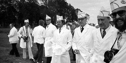Arkivbild i svart och vitt från 1970-talet med Sveriges konung och en massa glada män i vita rockar och matchande hattar.