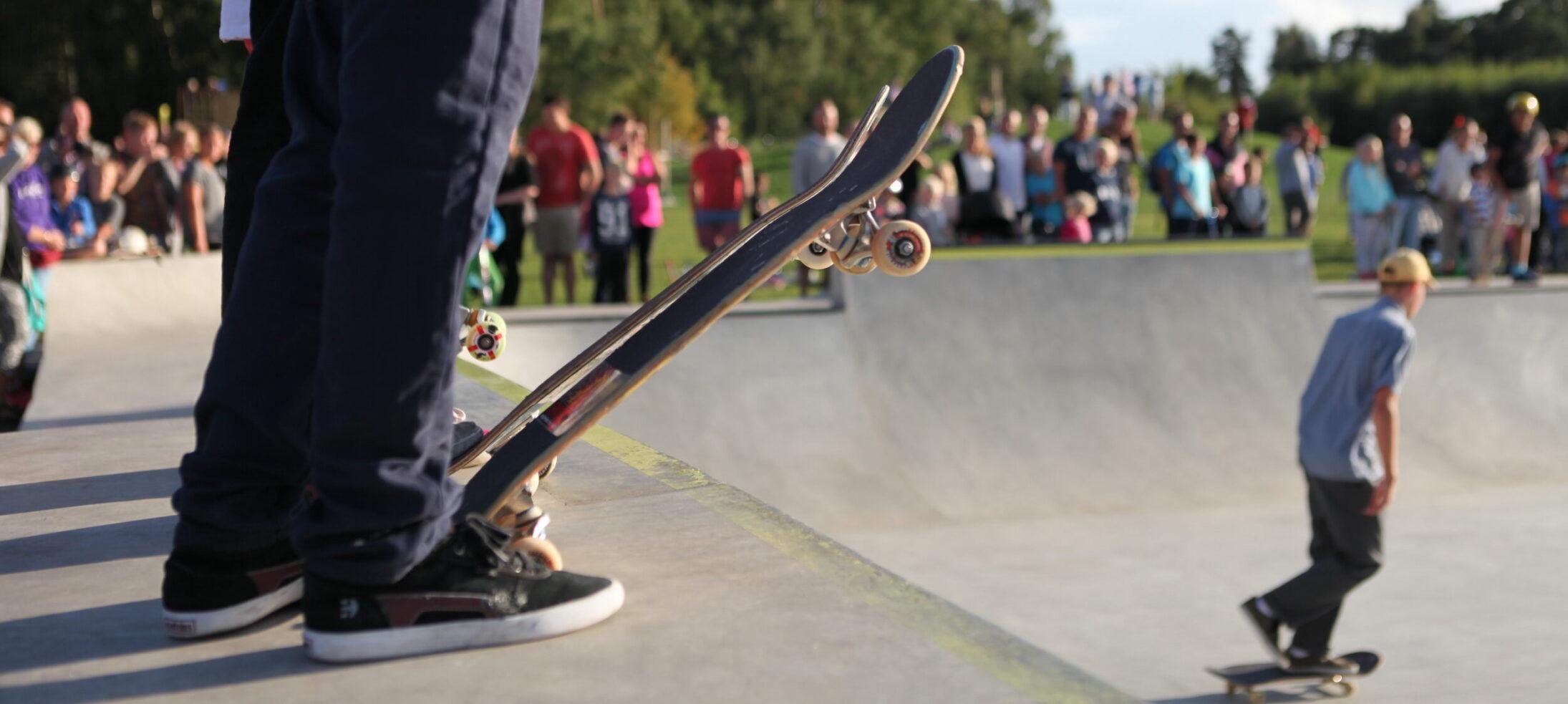 Närbild på ben i jeans och gympaskor med skateboard vid ramp i betong. Publik i förgrunden och kille på skateboard.