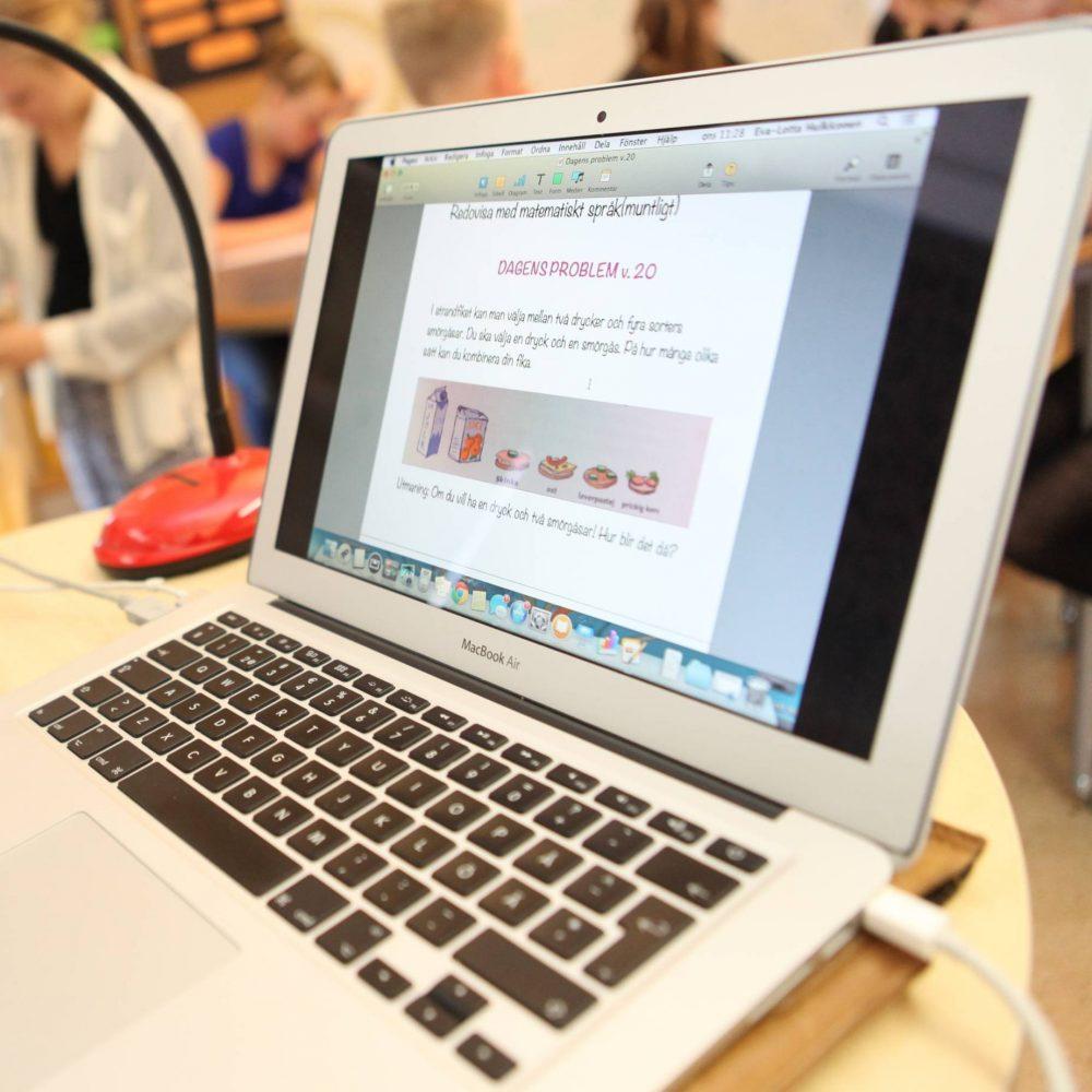 Lärare i tröja och skjorta sitter framför sin laptop i klassrummet och tittar glatt in i kameran.